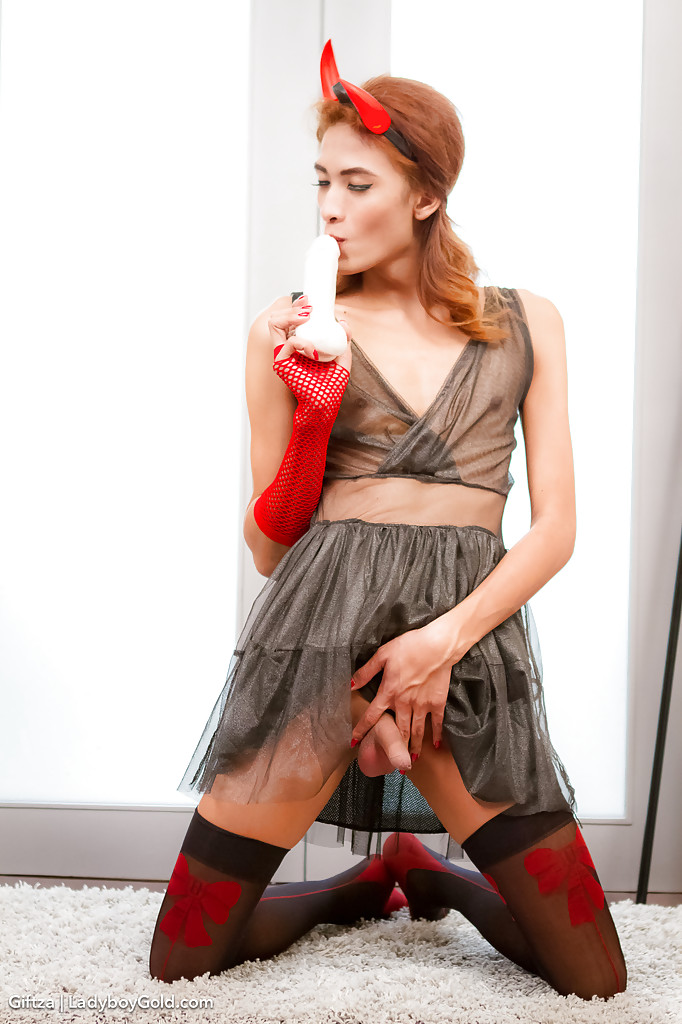 Redhead ladyboy poses in skirt and corset while stroking 9